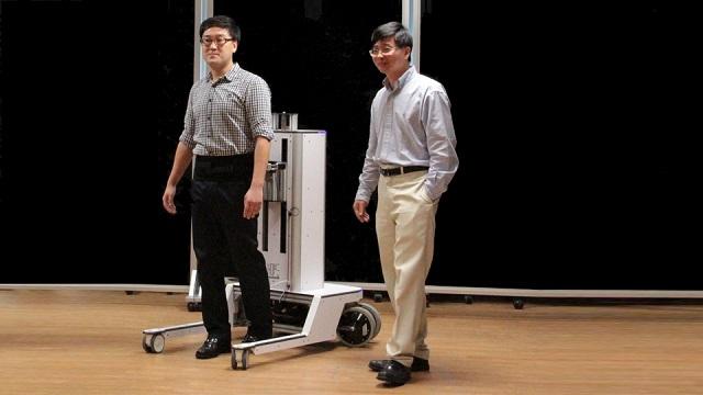 Разработчики демонстрируют своё творение – аппарат, предназначенный для восстановления утраченной способности ходить (фото National University of Singapore).